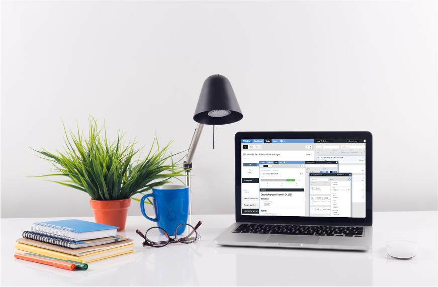Ein Schreibtisch mit einem Notebook, auf dem Bildschirm ist das Programm TRINOM Task zu sehen.